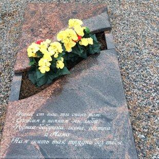 10. Granīta kapu apmalīte daļēji slēgta ar gravējumu un vietu ziedu apstādījumam